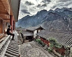 A backpacker sit in the corridor to look at the Jade Dragon Snow Mountain. Teahorse GH