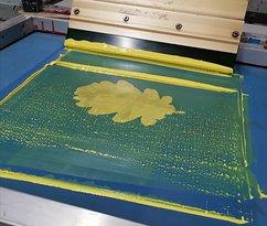 Application d'encre jaune, dans l'atelier de sérigraphie.