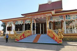 The entrance to the Pavilion building has around 8 blue steps with an orange strip down the centre and flanked by two dragon figures on either side.   The building's frontage is open to the elements with no walls.  It has an ornate white vase-like railing at the base and at the top overhanging from the roof along the outer top edge are what I describe as very attractive semi circular carved-out panels with murals on both the panels' exterior and interior.