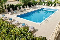 Outdoor swimming pool with sun loungers, beach chairs and sun umbrellas