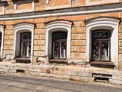 Окна первого этажа декорированы значительно скромнее