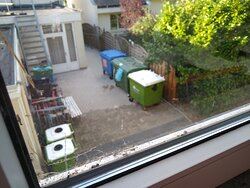 courtyard behind the kitchen, dirty old windows that do not close properly.