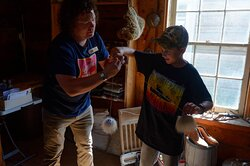 Tour guide Michael helping our son master a historic toy that requires a lot of coordination!