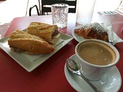 Café con leche, pasta, bocadillo y botella de agua.