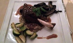 Lamb shank with mushrooms and grilled vegetables.