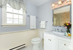 Newly renovated spa bathroom with glass-enclosed step-in shower and large marble vanity