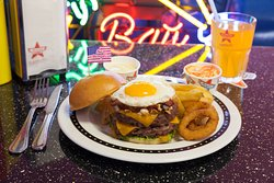 KINGS BURGER Bun brioché, viande hachée de bœuf fraîche, œuf à cheval, poitrine fumée, crispy onions, cheddar, salade et sauce Texas