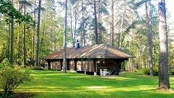 Rooms in log cabins in large area with old trees and beside the bond. Hirsimökeissä majoitushuoneita puistoalueella, jossa paljon vanhoja puita ja lampi.