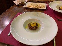 Plato 4. Umami: Tartar de lomito ibérico, mojama de Isla Cristina, agua de tomatillos verdes y yema de huevo inyectada con caldo de jamón concentrado.