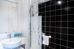 Salle de bain avec douche ou baignoire avec produits d'accueil, sèche-cheveux, serviettes...