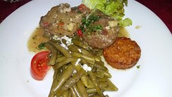 Joues de porc à la provençale accompagnées d'haricots verts frais et d'une galette de pomme de terre.