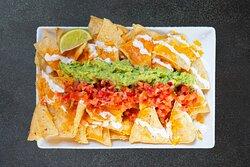 Nachos à partager : envie de réaliser cette superbe assiette ? Voici le kit complet pour des nachos à partager savoureux : nachos (tortilla chips), cheddar anglais affiné 🧀 (à faire fondre vous-même), notre salsa pico de gallo 🍅, notre célèbre guacamole 🥑 et de la sour cream 🥛