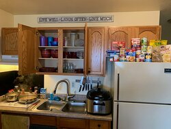 Only cabinet not locked is full of dishes, so food must be stored on top of refrigerator