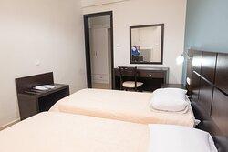 Δίκλινο δωμάτιο με δύο μονά κρεβάτια και θέα στο άλσος της Αγίας Παρασκευής.