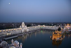 The moon at dawn, over the Golden Temple, as if reluctant to let go.