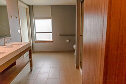The bathroom has the space and feel of a commercial building restroom facility.