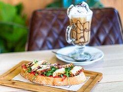 Café con tostada de pollo, tomate natural y rúcula.