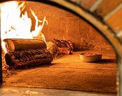 C'est dans notre four à bois que nos plats sont préparés, pour une cuisson parfaite et un goût exceptionnel qui en fait baver plus d'un.
