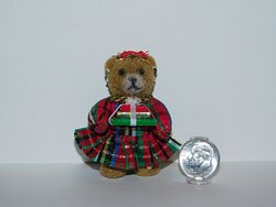 Brown bear wearing plaid dress and holding presents by Cheryl Warder