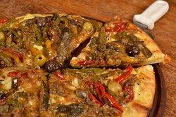 Pizza Vegetariana. Ingredientes: molho de tomate italiano, mussarela, legumes ao wok (pimentão 3 cores, cebola e beringela), azeitonas e orégano.
