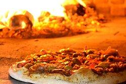 As pizzas da Casa Grecia são assadas no forno a lenha.