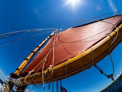 The beautiful crimson sails and natural wood masts of the Edith M. Becker.