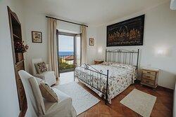 Camera da letto matrimoniale del bilocale 3 con balcone e vista mare.