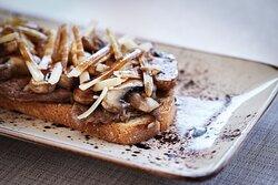 Tosta de solomillo de res, queso grana padano y champiñones.