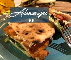 Primer plano de nuestro almuerzo de Cotoletta casera, empanada por nosotros y puesta sobre nuestro panino, con mayonesa, brotes variados y tomate fresco.