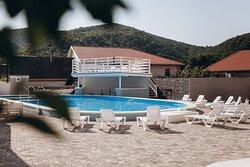 Просторная территория отеля с зоной отдыха вокруг бассейна. Не выходя из воды можно воспользоваться баром у воды и заказать прохладительный напиток.