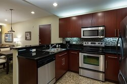 State of the art kitchen with fridge, microwave, stove with oven.