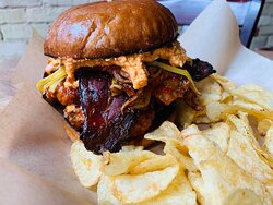 Fried local chicken thigh glazed with sweet and spicy sticky sauce, house bacon, gochujang pickled shallots, kimchi, and pimento cheese on an artisan bun. Served with chips.