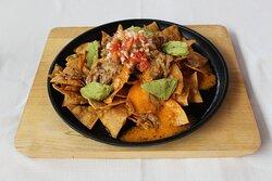 Nachos costilla tex-mex  Totopos caseros, guacamole, salsa cheddar, pico de gallo y costilla tex-mex a baja temperatura