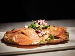 Tosta de salmón ahumado sobre una base de aguacate y mix de lechuga