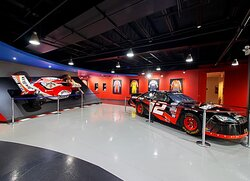 The Lobby at K1 Speed Buffalo Grove featuring some of the authentic motorsport memorabilia on display, including an IndyCar, NASCAR car and driver suits & helmets.