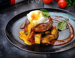 Большой сочный бифштекс, обжаренный на гриле. Подается с яйцом пашот, домашним картофелем и перечным соусом.