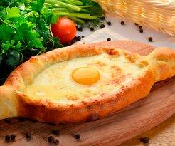 Традиционное кавказское блюдо из теста в форме лодочки, с большим количеством сыра и яйцом