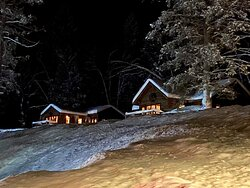 Top floor of cabins visible on a snowy night from behind the restaurant