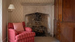 Comfy chair and feature fireplace in the Yate suite