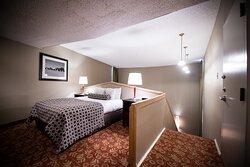One queen bed upper level of the Bi Level Suite