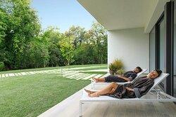 Zona relax/lettura esterna che affaccia su ampio prato verde