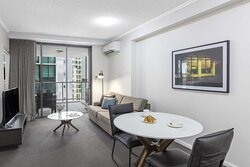 Interior view of lounge and dining area in One Bedroom Suite with city view