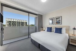Interior view of bedroom in Two Bedroom Suite with king bed and balcony view