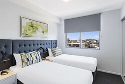 Interior view of bedroom in Two Bedroom Suite with twin beds and city view