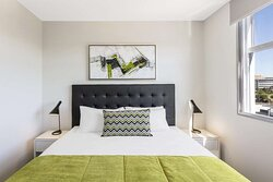 Interior view of bedroom in Two Bedroom Suite with city view
