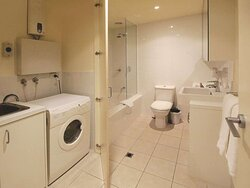 Interior view of bathroom in One Bedroom Suite with shower in bathtub and laundry appliances