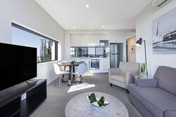Interior view of lounge, dining area and kitchen in Two Bedroom Executive Suite with city view