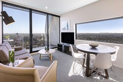 Interior view of lounge and dining area in Two Bedroom Executive Suite with city view