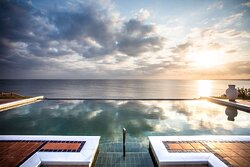 Exterior view of main swimming pool at sunrise with ocean view
