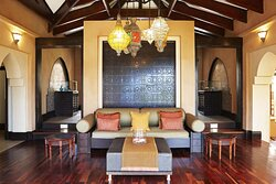Avani Spa relaxation area with wooden floors, a couch, ottoman and decorative screen and lighting